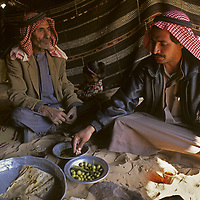 Bedouin men, wearing traditional kafiyeh and agals, share a meal in a wool nomad tent in the Wadi Rum, Jordan.