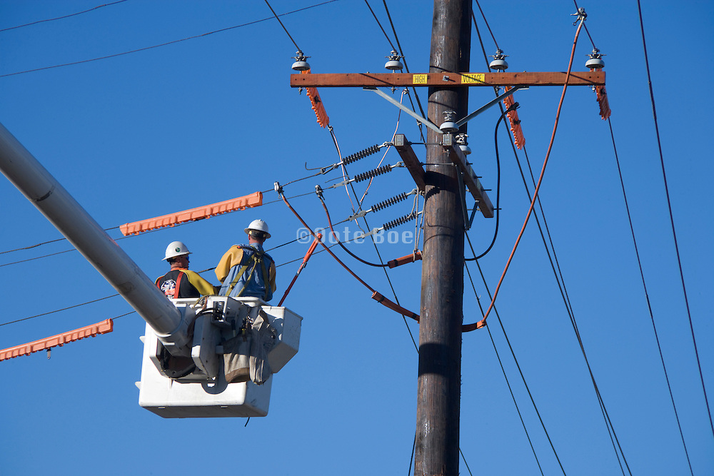construction workers working on above ground placed electrical wires USA