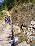 Crossing a small bridge over a stream along the Camino Salkantay, Peru.