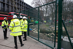 London, UK. 31 January, 2021. HS2 workers stand alongside a tree in Euston Square Gardens recently felled on behalf of HS2 Ltd. Members of the National Eviction Team (NET) are currently evicting anti-HS2 activists from umbrella campaign group HS2 Rebellion from a camp and tunnels in Euston Square Gardens where they have been seeking to protect trees from felling in connection with the controversial HS2 high-speed rail project.