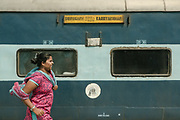 A woman wearing a pink dress breezes past the second class compartment.<br /> Outside the Dibrugarh-Kanyakumari Vivek Express, the longest train route in the Indian Subcontinent. It joins Kanyakumari, Tamil Nadu, which is the southernmost tip of mainland India to Dibrugarh in Assam province, near the border with Burma.