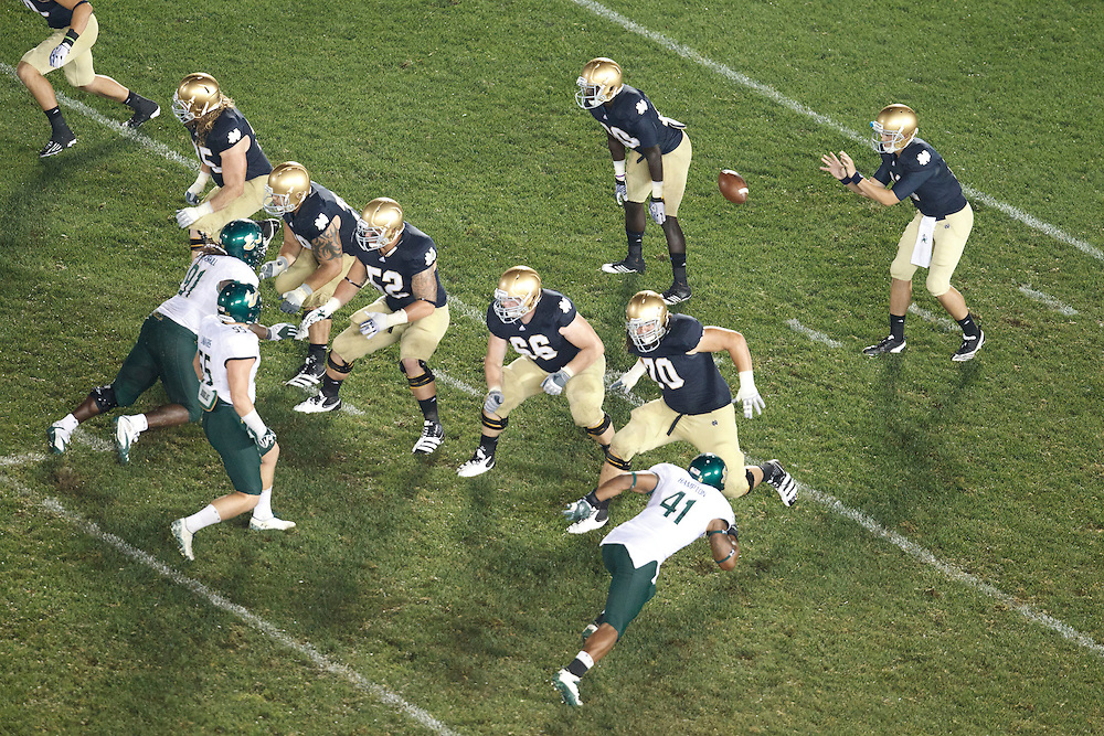 A general view of play as Notre Dame quarterback Tommy Rees (#11) receives snap in action during NCAA football game between Notre Dame and South Florida.  The South Florida Bulls defeated the Notre Dame Fighting Irish 23-20 in game at Notre Dame Stadium in South Bend, Indiana.