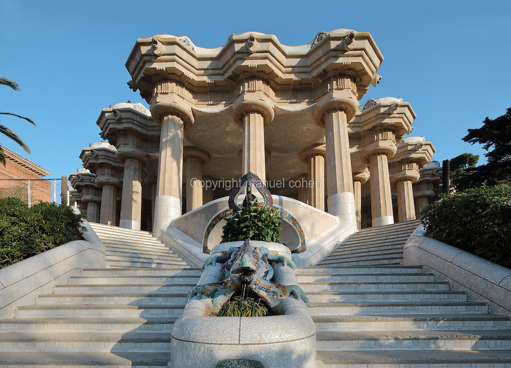 Lower Court on the central terrace, with Doric columns supporting a hypostyle hall and stone roof lined with mosaics, at Park Guell, built 1900-14 by Antoni Gaudi, 1852-1926, Catalan Modernist architect, on Carmel Hill, Barcelona, Catalonia, Spain. On the staircase is 'el drac' (the dragon), a mosaic salamander fountain, restored in 2007. The park was commissioned by Eusebi Guell and opened in 1926. The area was designed to hold public gardens, houses, paths and roads, irrigation systems and a terrace. Gaudi used organic forms in the structures of the park, incorporating symbols from Catalan nationalism, religious mysticism and ancient poetry and mythology. It is listed as a UNESCO World Heritage Site. Picture by Manuel Cohen