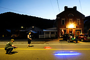 """Chelsea, Vt., residents Rob Knudsen, left, Dylan O'Dell, middle, and Travis Watson, right, gather near the town green Wednesday night, June 10, 2021, for RC car drag races. Weather permitting, the friends race the cars, which run up to 44 mph and use GPS to give feedback on a phone app, up to four nights a week. """"There's far worse things people are doing in town than running their RC cars,"""" said Watson. """"There's not much else to do in Vermont,"""" said Knudsen. (Valley News - James M. Patterson) Copyright Valley News. May not be reprinted or used online without permission. Send requests to permission@vnews.com."""