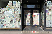 Sheets of old newspapers cover the window of the closed branch of 'All Bar One' on New Oxford Street, during the third lockdown of the Coronavirus pandemic, on 29th March 2021, in London, England.