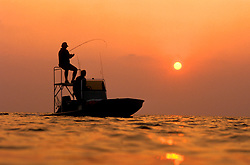 Stock photo of the silhouette of two fishermen fishing from a boat at sunset.