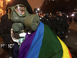 January 20, 2017 - Washington, District of Columbia, U.S. - A protester with a gas mask checks her surroundings as police move crowds back at nightfall. (Credit Image: © Kevin G. Hall/TNS via ZUMA Wire)