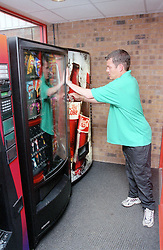 Man with disability unlocking vending machine in leisure centre,
