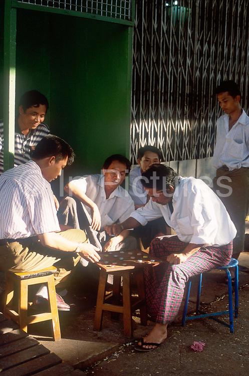 Men playing chequers using bottletops, during an afternoon break. Rangoon, Burma 2001