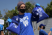 Actor Niko Guardado hands out care packages at the Dodger Day Drive-Thru at Belvedere Park, Tuesday, June 30, 2020, in Los Angeles. The event was hosted by The Los Angeles Dodgers Foundation, which distributed food boxes, books, sports equipment, clothing, toys and hygiene supplies to more than 1,000 registered youth from the Boyle Heights, East Los Angeles, La Puente and Monterey Park communities.