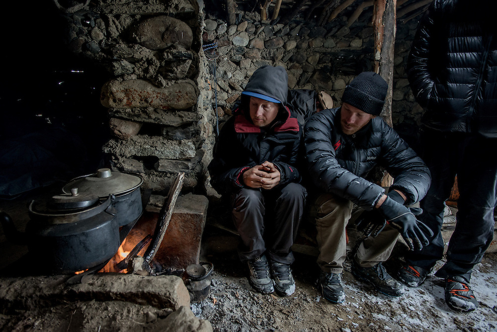 Matt Hunter and CJ huddle near Amin Beg's cooking fire, inside a draughty shepherds hut during a day of blizzards. Karabel camp, 4300m.