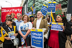 London, UK. 15 July, 2019. Mark Serwotka, Fran Heathcote and Zita Holbourne of the PCS trade union pose with catering and cleaning staff outsourced to work at the Department for Business, Energy and Industrial Strategy (BEIS) via contractors ISS World and Aramark on the picket line outside the Government department after walking out on an indefinite strike for the London Living Wage, terms and conditions comparable to the civil servants they work alongside and an end to outsourcing.