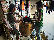 "05 OCTOBER 2015 - BANGKOK, THAILAND: Workers pack a resident's ""khlong jar"" on moving day in the Wat Kalayanamit neighborhood. Khlong jars are large ceramic jars used to store domestic water in homes that don't have municipal water. The people moving were being evicted from their homes. Fifty-four homes around Wat Kalayanamit, a historic Buddhist temple on the Chao Phraya River in the Thonburi section of Bangkok, are being razed and the residents evicted to make way for new development at the temple. The abbot of the temple said he was evicting the residents, who have lived on the temple grounds for generations, because their homes are unsafe and because he wants to improve the temple grounds. The evictions are a part of a Bangkok trend, especially along the Chao Phraya River and BTS light rail lines. Low income people are being evicted from their long time homes to make way for urban renewal.        PHOTO BY JACK KURTZ"