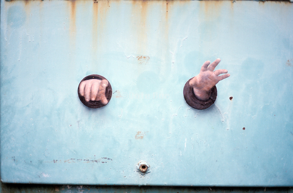 hands glued on a metal wall