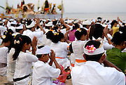 Devotees praying, Hindu religious ceremony on beach, celebrating Galungan. Galungan celebrates the victory of virtue (Dharma) over evil (Adharma) and is perhaps the most important religious holiday for Balinese Hindus. Sanur, Bali, Indonesia