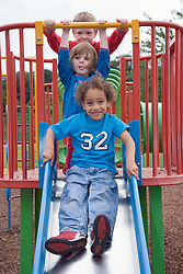 Little children playing on a slide,