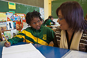 An African school child looks at her volunteer literacy teacher in a classroom in Observatory Primary School, Cape Town, South Africa.  The teacher is spelling a word that the child is trying to write in her exercise book. The volunteer teachers have been provided to the school by Shine Centre which is a charity that aims to address the high illiteracy rate in South Africa by improving literacy levels among children in schools and disadvantaged communities.