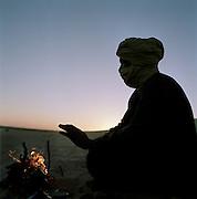 Tuareg Tribesman warming his hands by the fire at dawn, Sahara Desert, Libya
