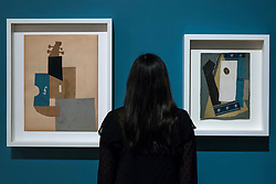 """© Licensed to London News Pictures. 21/01/2020. LONDON, UK. A staff member views (L to R) """"Violin"""", 1912, and """"Guitar"""", 1913, both by Pablo Picasso at the preview of """"Picasso and Paper"""", an exhibition at the Royal Academy of Arts, which is the most comprehensive exhibition ever devoted to Pablo Picasso's imaginative and original uses of paper .  Over 300 works both on and with paper, are on display 25 January to 13 April 2020.  Photo credit: Stephen Chung/LNP"""