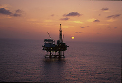 Stock photo of an offshore jack-up drilling rig at sunset