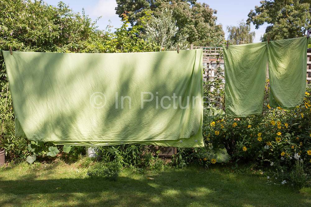 Green sheets dry on a washing line in a back garden of a south London residential house, on 18th August 2019, in London, England.