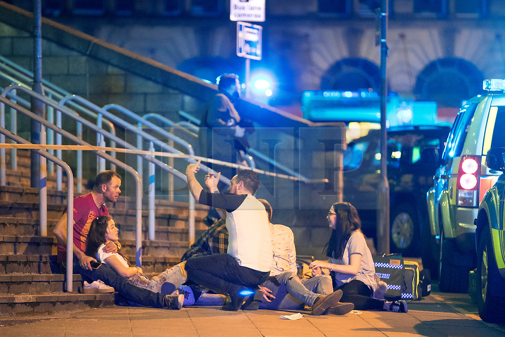 © Licensed to London News Pictures . FILE PICTURE DATED 22/05/2017 as Manchester prepares to mark a year since the Manchester Arena terror attack . Manchester, UK. Wounded people on Hunts Bank outside Victoria Station and the stairs leading to the Manchester Arena . Police and other emergency services are seen near the Manchester Arena after Salman Abedi murdered 22 and injured dozens more at an Ariana Grande concert at Manchester Arena. Photo credit : Joel Goodman/LNP