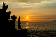 A Balinese man in traditional dress and headgear, gazes out at the setting sun.