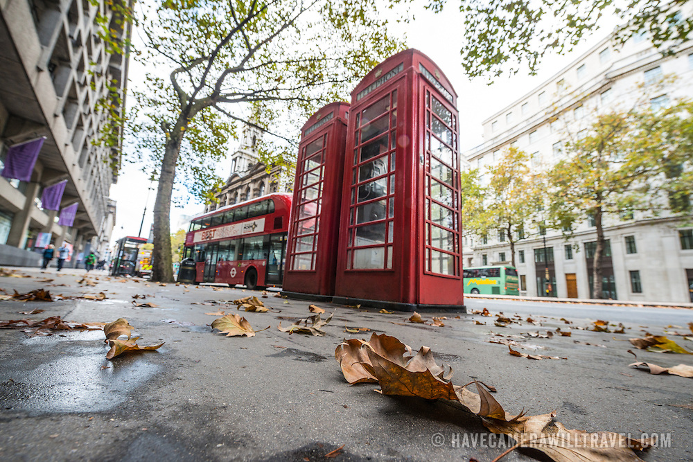 Autium leaves on the footpath in central London in front of a pair of red telephone boxes and a red double-decker bus on the Strand.