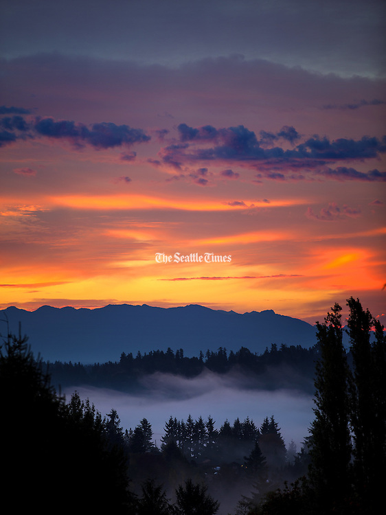 The sun creates a colorful scene as it rises over the Cascade Mountain Range above a bank of fog in this view from Horizon View Park near the Lake Forest Park reservoir. (Mike Siegel / The Seattle Times)