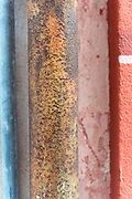 A colorful pipe with orange-yellow rust and two red and blue building support columns adorn a building in Bonasollo, Italy