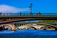 Pedestrians cross Pont d'Arcole,  one of the many bridges over the RIver Seine, Paris, France.
