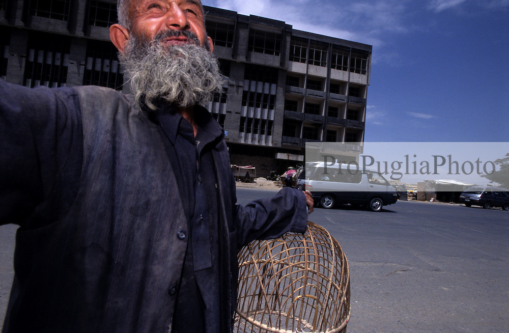 An old man carrying a birdcage