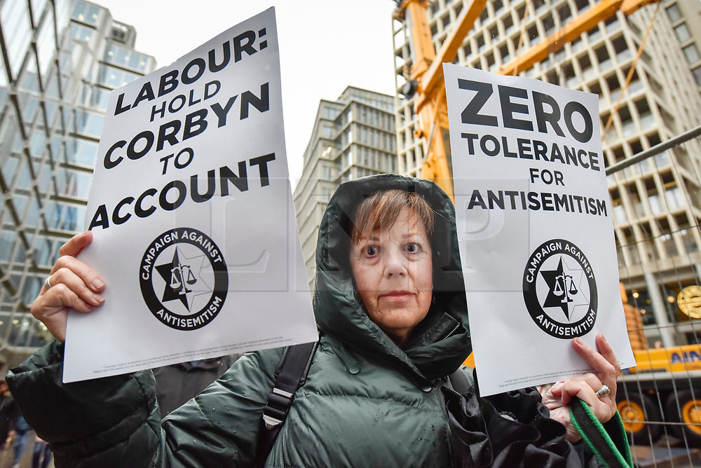 © Licensed to London News Pictures. 08/04/2018. LONDON, UK. A woman poses with signs at a protest calling for Jeremy Corbyn, leader of the Labour party, to be held to account.  The event was organised by the Campaign Against Anti-Semitism, outside the Labour Party's headquarters in central London.  Photo credit: Stephen Chung/LNP