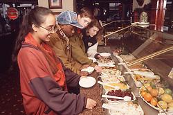 Multiracial group of teenagers at selfservice salad bar,
