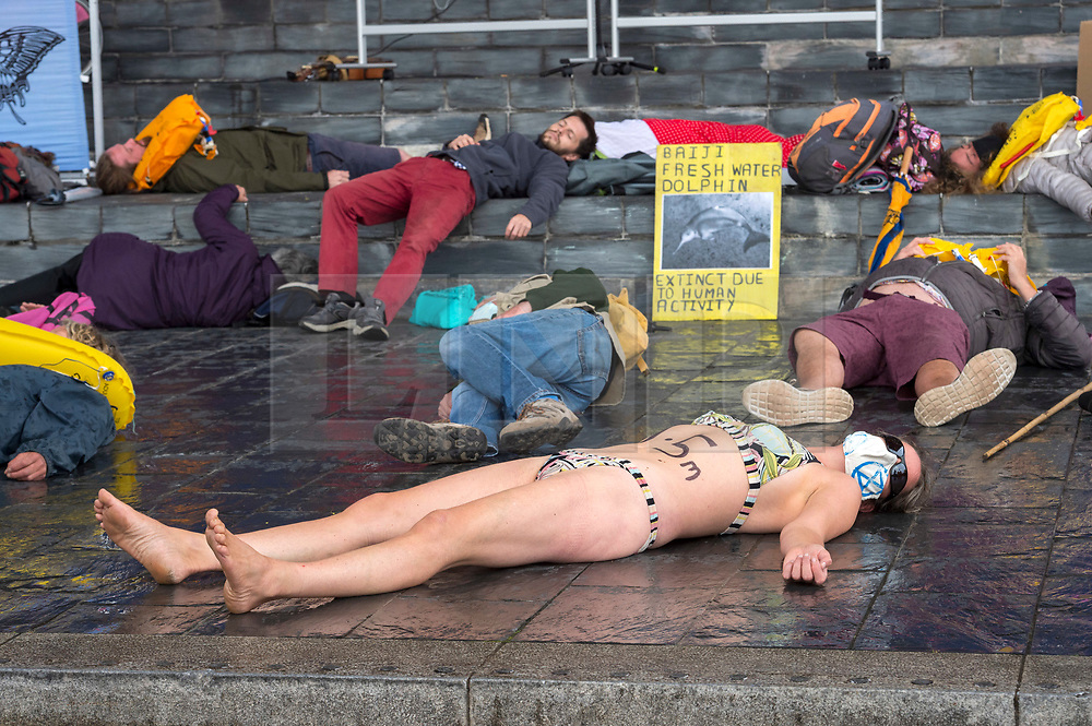 """© Licensed to London News Pictures;02/09/2020; Cardiff, Wales, UK. A woman in a swimming costume takes part in a """"drown in"""" at an Extinction Rebellion protest in Cardiff Bay in front of the Senedd, the Welsh Government building, in support of the upcoming Climate and Ecological Emergency Bill. She has 1.5m painted on her torso referring to projected rises in sea levels. Today the protest is """"Rising Tide Action!!"""" focusing on the impact that the climate crisis is having locally and across Wales because it is impacting weather cycles, flooding, air pollution and our food security. The protest involved arts, theatre, speakers, music, banners and a drown in. The protest is part of a national protest over the next two weeks including London and other cities in the UK against climate change. XR say that despite clear scientific evidence of the deadly climate and ecological emergency, the UK government are refusing to take the urgent action needed to avoid mass extinction, and that politicians need to support the Climate and Ecological Emergency Bill. During the coronavirus covid-19 pandemic, climate change is being forgotten but it is still an emergency that is happening. The protest was socially distanced and participants wore masks. Photo credit: Simon Chapman/LNP."""