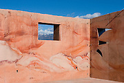 Red earth house with mountains and sky<br />