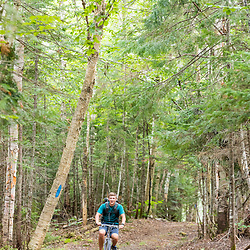 A boy rides his mountain bike on the Gardner Loop Trail, near Crater Pond in Aroostook County, Maine. Deboullie Public Reserve Land.
