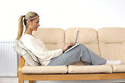 women with a laptop computer sitting on a sofa, home office,<br />