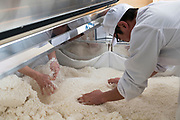 Distillery staff mix rice in the koji making machine, Nekka Shochu Distillery, Tadami, Fukushima, Japan, February 22, 2018. The Nekka shochu distillery was founded in July 2016 and at that time was the smallest shochu distillery in Japan. It makes shochu from locally-grown rice, and is helping support a local economy that has languished since the nuclear disaster of 2011.
