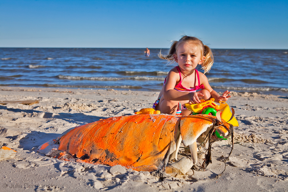 Young girl plays next to a dead sea turtle on the beach in Pass Christian. An unprecedented number of dead young  Kemp's Ridley and Loggerhead  sea turtles have washed up on the shores of Mississippi along the Gulf of Mexico starting almost a year after the BP oil spill. <br /> Test are being done on the high number of turtle and dolphin corpses found on the beaches but results have not been released.