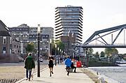 Nederland, Nijmegen, 6-10-2020 Langs de Waal bij Nijmegen . De Waal is het Nederlandse deel van de Rijn en de belangrijkste vaarroute van en naar Rotterdam en Duitsland . De waalkade geeft veel ruimte voor ontspanning, wandelen en recreatie . Op de achtergrond de spoorbrug en de nieuwbouw op de handelskade, de Lunet .Foto: ANP/ Hollandse Hoogte/ Flip Franssen