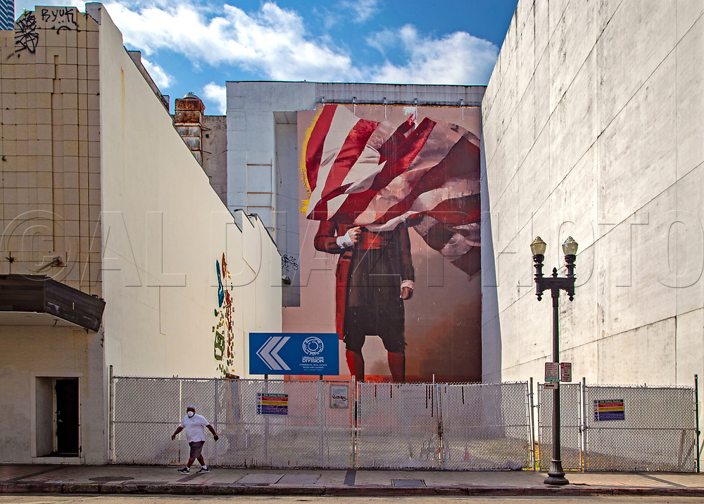Fernando Boigs is seen wearing a protective mask as he walks under a large mural along Flagler Street during the COVID19 pandemic in downtown Miami on Wednesday, April 1, 2020.