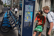 Tourists look at a London map and information about renting a TFL 'Boris' bike. The visitors to the UK capital have stopped to read rental and payment instructions at this post that are located throughout London at strategic points, for tourists and Londoners too. The Barclays bank-sponsored bikes (aka 'Boris bikes' after the cycling hire initiative introduced by London Mayor Boris Johnson) are lined up in the background and a map showing the immediate area of this loaction in the City of London, the heart of the capital's financial district, founded by the Romans in AD43.