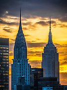 The Empire State Building and The Chrysler Building stand side by side in the cityscape of New York City.