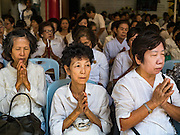 """31 JANUARY 2016 - BANGKOK, THAILAND: People participate in a prayer service before Chinese New Year at Wat Mangon Kamlawat, the largest Mahayana (Chinese) Buddhist temple in Bangkok. Thailand has the largest overseas Chinese population in the world; about 14 percent of Thais are of Chinese ancestry and some Chinese holidays, especially Chinese New Year, are widely celebrated in Thailand. Chinese New Year, also called Lunar New Year or Tet (in Vietnamese communities) starts Monday February 8. The coming year will be the """"Year of the Monkey.""""            PHOTO BY JACK KURTZ"""