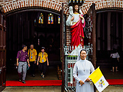 26 NOVEMBER 2017 - YANGON, MYANMAR: A Catholic nun in front of St. Mary's Cathedral in Yangon after buying flags (Vatican flag left, Myanmar flag right) honoring the visit of Pope Francis to Myanmar. The Pope will visit Yangon November 27 - 30. He will have private meetings  with government officials, military leaders and Buddhist clergy. He will also participate in two masses, a public mass in a sports complex on November 29 and a mass for Myanmar youth in St. Mary's Cathedral on November 30.    PHOTO BY JACK KURTZ