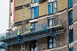 Glasgow, Scotland, UK. 23 March 2021. New cladding on  high-rise apartment building under construction  has been removed  and is being replaced with a traditional brick outer wall. The cladding was possibly removed because it did not comply with new fire retardation regulations. Iain Masterton/Alamy live News