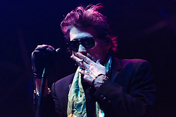 © Licensed to London News Pictures. 20/12/2012. London, UK.   Shane MacGowan of The Pogues smokes a cigarette as they perform live at The O2 Arena for their only UK live date of 2012 as part of their 30th Anniversary Tour.  The Pogues are a Celtic punk band from London, formed in 1982 and fronted by Shane MacGowan.  Members include Shane MacGowan (vocals, guitar, banjo, bodhrán),.Spider Stacy (vocals, tin whistle), Jem Finer (banjo, mandola, saxophone, hurdy-gurdy, guitar, vocals), Andrew Ranken (drums, percussion, harmonica, vocals), .James Fearnley (accordion, mandolin, piano, guitar), .Philip Chevron (guitar, vocals),  Darryl Hunt (bass guitar),.Terry Woods (mandolin, cittern, concertina, guitar, vocals).     Photo credit : Richard Isaac/LNP