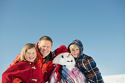 Portrait of family with snowman, smiling, Bavaria, Germany