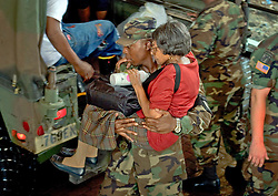 30 August, 2005. New Orleans Louisiana. Hurricane Katrina aftermath. <br /> Rescued from the flooded lower 9th ward by the Louisiana National Guard, an elderly woman is carried to safety at the makeshift hospital triage unit set up at the Superdome in New Orleans.<br /> Photo Credit: Charlie Varley/varleypix.com